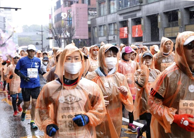 In this Feb. 16, 2020, photo, runners, some wearing masks, compete in a Kumamoto castle marathon in Kumamoto city, western Japan. Organizers of the Tokyo Marathon set for March 1, 2020 are drastically reducing the number of participants out of fear of the spread of the coronavirus from China. The general public is essentially being barred from the race. (Kyodo News via AP)