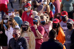 People wait in line for an exhibit at the NFL Experience Thursday, Feb. 4, 2021, in Tampa, Fla. The city is hosting Sunday's Super Bowl football game between the Tampa Bay Buccaneers and the Kansas City Chiefs. (AP Photo/Charlie Riedel)