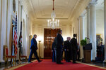 President Donald Trump, left, arrives to address the nation on the ballistic missile strike that Iran launched against Iraqi air bases housing U.S. troops, at the White House, Wednesday, Jan. 8, 2020, in Washington. (AP Photo/Alex Brandon)