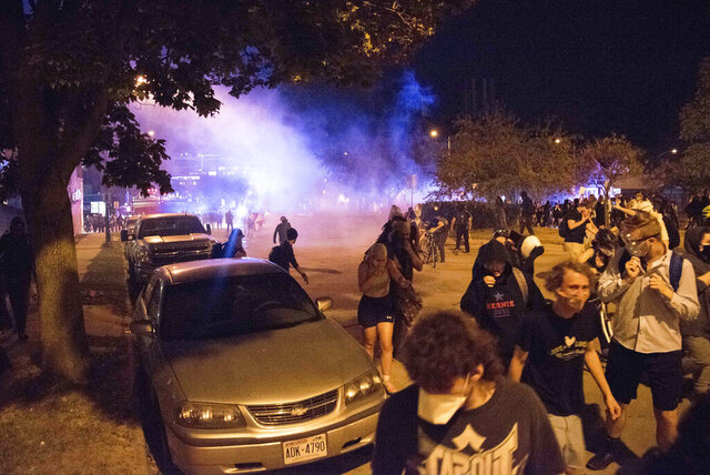 A crowd disperses as police deploy tear gas during a protest in downtown Madison, Wis., on Aug. 24, 2020. The protest came in response to the police shooting of Jacob Blake in Kenosha, Wis., one day earlier. (Will Cioci/Wisconsin Watch via AP)