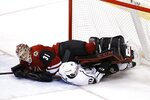 Los Angeles Kings center Tobias Rieder (10) takes out Arizona Coyotes goaltender Adin Hill (31) during the second period of an NHL hockey game Tuesday, March 13, 2018, in Glendale, Ariz. (AP Photo/Ross D. Franklin)