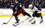 Columbus Blue Jackets forward Josh Anderson, left, shoots the puck against Boston Bruins defenseman Brandon Carlo during the second period of an NHL hockey game in Columbus, Ohio, Tuesday, March 12, 2019. (AP Photo/Paul Vernon)