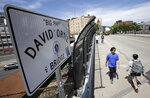 Passers-by walk over a bridge named for former Boston Red Sox slugger David Ortiz near Fenway Park, in Boston, Monday, June 10, 2019. Ortiz was ambushed by a man who got off a motorcycle and shot him in the back at close range Sunday night in his native Dominican Republic, authorities said. (AP Photo/Steven Senne)