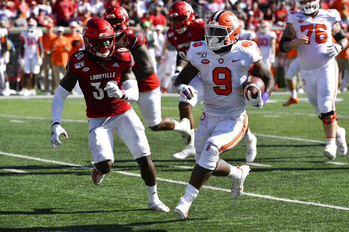 Clemson running back Travis Etienne (9) runs from the pursuit of Louisville defensive back Khane Pass (30) during the second half of an NCAA college football game in Louisville, Ky., Saturday, Oct. 19, 2019. Clemson won 45-10. (AP Photo/Timothy D. Easley)