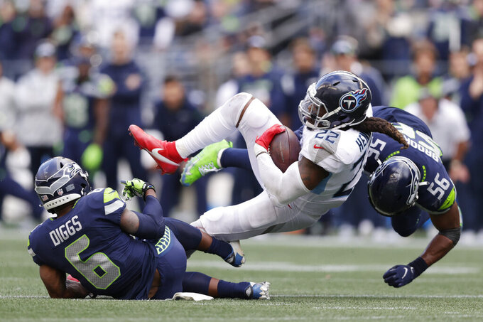 Tennessee Titans running back Derrick Henry (22) is tackled by linebacker Jordyn Brooks (56) and strong safety Quandre Diggs (6) during the second half of an NFL football game, Sunday, Sept. 19, 2021, in Seattle. The Titans won 33-30 in overtime. (AP Photo/John Froschauer)