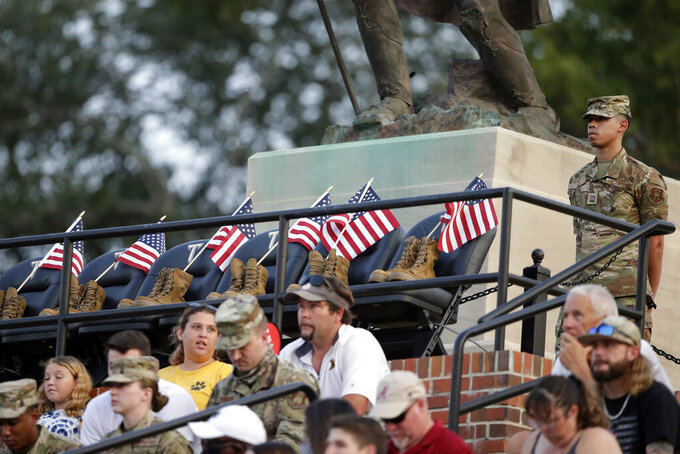 A Troy Army ROTC member stands guard over seats honoring the 13 soldiers killed recently in Afghanistan, during the first half of an NCAA college football game between Troy and Liberty, Saturday, Sept. 11, 2021, in Troy, Ala. (AP Photo/Butch Dill)