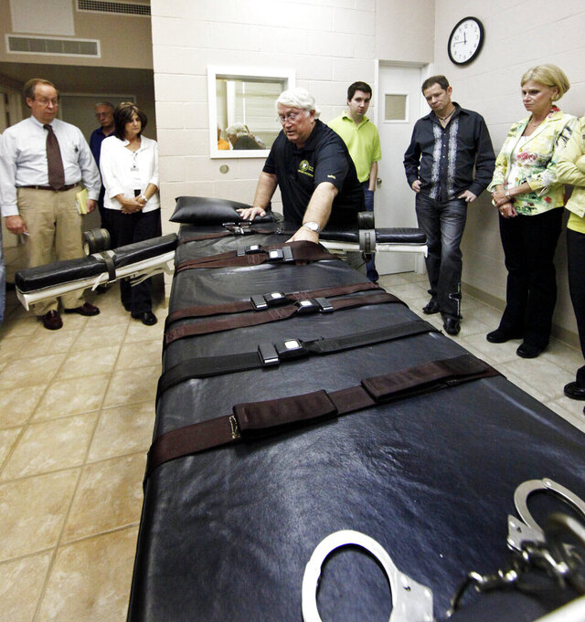 FILE - In this Sept. 18, 2009, file photo, Warden of the Louisiana State Penitentiary, Burl Cain, discusses the gurney used for lethal injections to Ruth Graham, far right and others as they visit the Louisiana State Penitentiary in Angola, La. Louisiana cleans its execution chamber at the state penitentiary daily, but it's been more than a decade since a condemned prisoner has laid on the chamber's black-padded gurney to die. Sixty-eight people sit on Louisiana's death row, with no execution dates set. Though the state historically has been tough on crime and holds the dubious distinction as the nation's incarceration capital, Louisiana seems to be doing very little to carry out its death penalty. (AP Photo/Judi Bottoni, File)