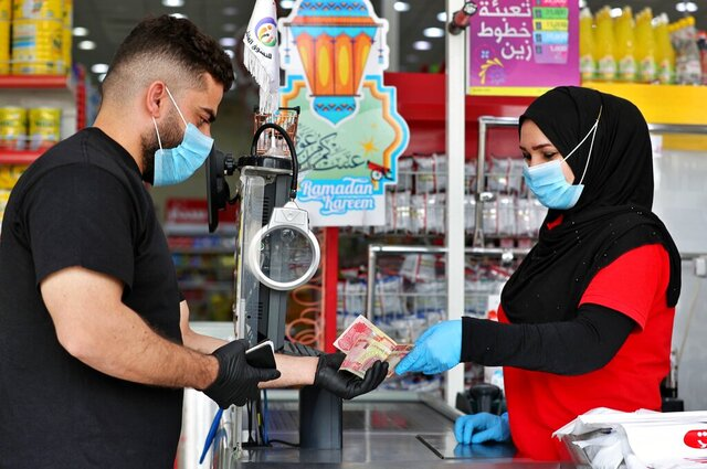 In this Saturday, May, 2, 2020, photo, a man uses banknotes to pay for his purchases at the mall in Basra, Iraq. The coronavirus pandemic has reawakened debate about the continued viability of what has been the physical lifeblood of global economies: paper money and coins.  (AP Photo/Nabil al-Jurani)