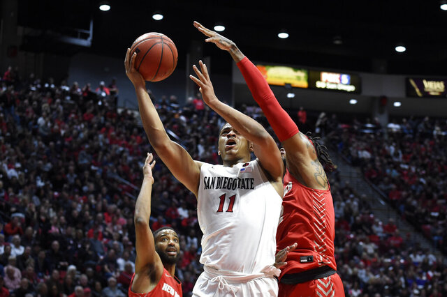 San Diego State forward Matt Mitchell (11) shoots past the defense of New Mexico guard Vance Jackson (2) during the first half of an NCAA college basketball game Tuesday, Feb. 11, 2020, in San Diego. (AP Photo/Denis Poroy)