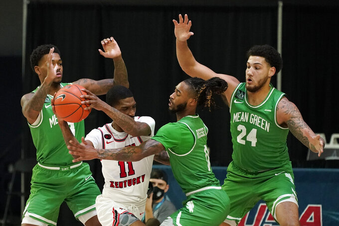Western Kentucky guard Taveion Hollingsworth (11) tries to pass around North Texas guard Javion Hamlet, left, guard James Reese (0) and forward Zachary Simmons (24) during the first half of the championship game in the NCAA Conference USA men's basketball tournament Saturday, March 13, 2021, in Frisco, Texas. (AP Photo/Tony Gutierrez)