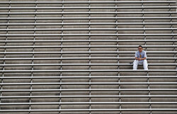 FILE - In this Nov. 17, 2012, file photo, any empty seats leaves this Arizona State fan all alone in the upper deck during an NCAA college football game against Washington State, in Tempe, Ariz. As lock-downs are lifted, restrictions on social gatherings eased and life begins to resemble some sense, sports are finally starting to emerge from the coronavirus pandemic. Many college and pro sports teams already were dealing with declining ticket sales. The improved at-home experience, the emergence of wide-spread legalized betting and the changing social makeup of fan bases have been catalysts, while dynamic pricing, increases in parking and concession prices and a push toward luxury seating have exacerbated the problem.(AP Photo/Ross D. Franklin, File)