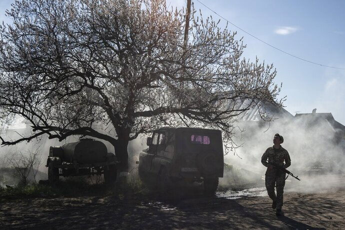 FILE - In this Saturday, April 20, 2019 file photo, a Ukrainian serviceman guards a position near the frontline as the conflict continues, in Mariinka, Donetsk region, eastern Ukraine. Volodymyr Zelenskiy, who takes the presidential oath on Monday May 20, 2019, comes into the post having never held political office; his popularity is rooted in playing the role of president on a television sit-com. (AP Photo/Evgeniy Maloletka, File)