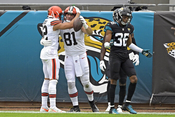 Cleveland Browns tight end Austin Hooper (81) celebrates his touchdown catch with wide receiver KhaDarel Hodge, left, as Jacksonville Jaguars cornerback Luq Barcoo (36) walks away dejected during the first half of an NFL football game, Sunday, Nov. 29, 2020, in Jacksonville, Fla. (AP Photo/Phelan M. Ebenhack)