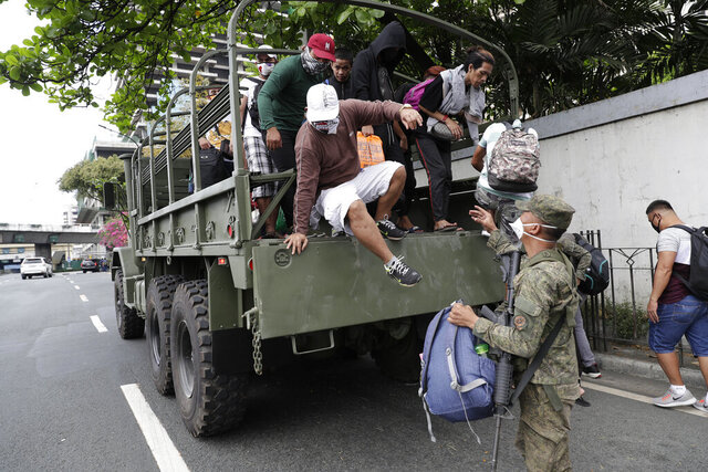 Commuters go down a military truck as they offer a free ride after public transportation have been halted due to the enhanced community quarantine to prevent the spread of the new coronavirus along an almost empty hi-way in Manila, Philippines on Wednesday, March 18, 2020. The Philippine government lifted a 72-hour deadline for thousands of foreign travelers to leave the country's main northern region which has been placed under quarantine due to the growing number of coronavirus infections, officials said. For most people, the new coronavirus causes only mild or moderate symptoms. For some, it can cause more severe illness, especially in older adults and people with existing health problems. (AP Photo/Joeal Calupitan)