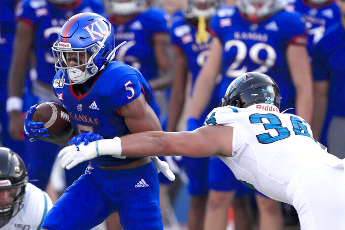 Kansas wide receiver Stephon Robinson Jr. (5) breaks away from Coastal Carolina linebacker Teddy Gallagher (34) during the first half of an NCAA college football game in Lawrence, Kan., Saturday, Sept. 7, 2019. (AP Photo/Orlin Wagner)