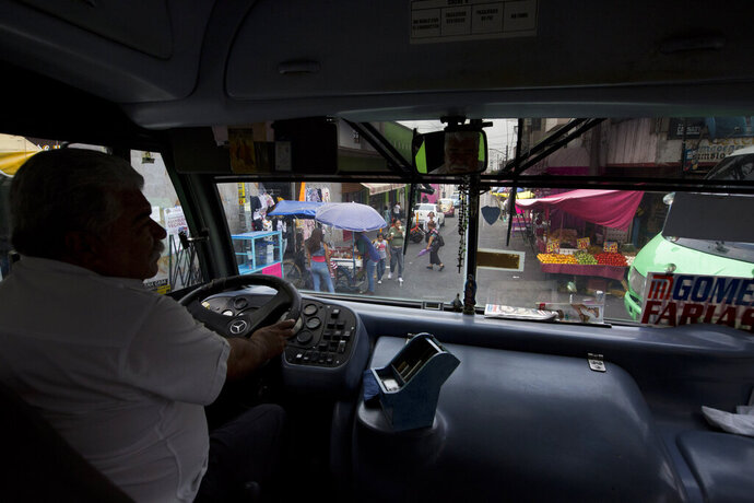 In this May 15, 2019 photo, a driver maneuvers through the narrow streets of San Miguel Teotongo on his bus where a pair of police officers ride along to protect him and his passengers from armed robbery in the Iztapalapa borough of Mexico City. Trigger-happy bandits regularly attack the buses that ferry people from the poorer outlying suburbs to jobs in the city center. (AP Photo/Rebecca Blackwell)