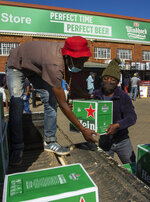 Workers load up purchased alcohol beverages outside the Sam Liquor Store in Thokoza township, near Johannesburg, South Africa, Monday, June 1, 2020.  Liquor stores have reopened Monday after being closed for over two months under lockdown restrictions in a bid to prevent the spread of coronavirus.(AP Photo/Themba Hadebe)