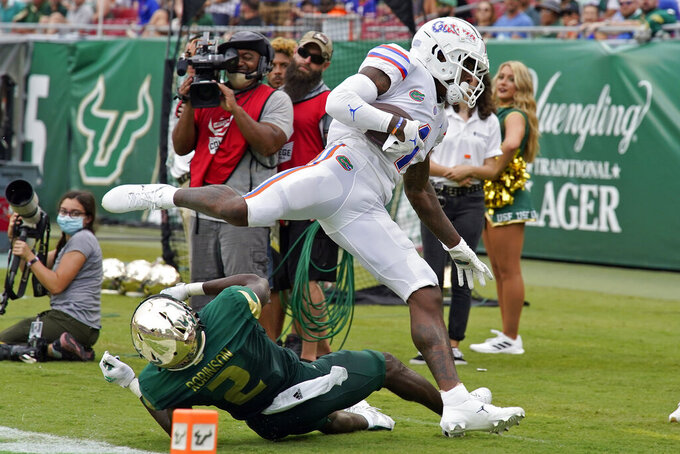 Florida wide receiver Jacob Copeland (1) hurdles over South Florida defensive back TJ Robinson after a catch during the second half of an NCAA college football game Saturday, Sept. 11, 2021, in Tampa, Fla. (AP Photo/Chris O'Meara)