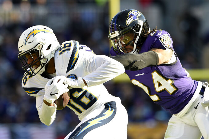 Los Angeles Chargers wide receiver Tyrell Williams, left, rushes past Baltimore Ravens cornerback Brandon Carr in the first half of an NFL wild card playoff football game, Sunday, Jan. 6, 2019, in Baltimore. (AP Photo/Gail Burton)