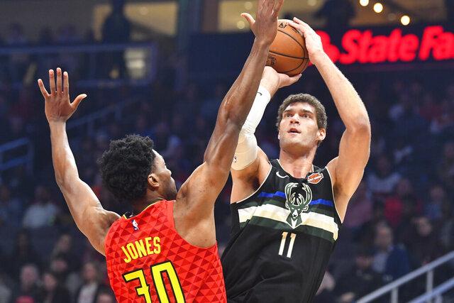 Milwaukee Bucks center Brook Lopez (11) shoots as Atlanta Hawks center Damian Jones defends during the first half of an NBA basketball game Friday, Dec. 27, 2019, in Atlanta. (AP Photo/John Amis)