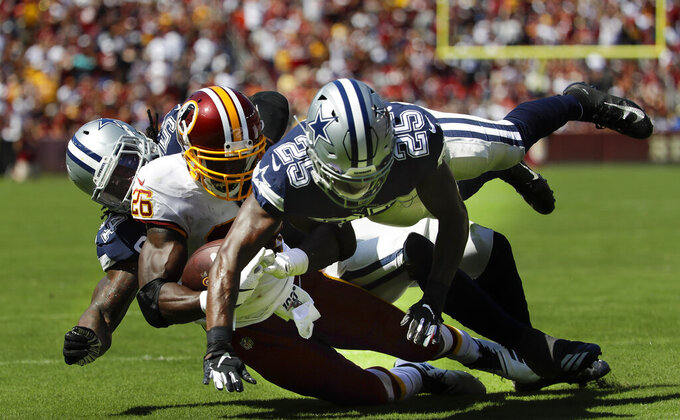 Washington Redskins running back Adrian Peterson (26) is stopped by Dallas Cowboys middle linebacker Jaylon Smith (54) and Dallas Cowboys free safety Xavier Woods (25) in the first half of an NFL football game, Sunday, Sept. 15, 2019, in Landover, Md. (AP Photo/Evan Vucci)