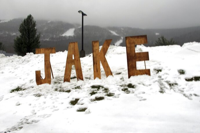 A wooden sign honoring snowboard pioneer Jake Burton Carpenter sits at the entranceway to a parking lot at Stowe Mountain Resort on Friday, Nov. 22, 2019, in Stowe, Vt. Snowboarders turned out to take turns down the mountain on opening day in honor of the founder of Burton Snowboards. Carpenter brought the snowboard to the masses and helped turn the sport into a billion-dollar business. (AP Photo/Lisa Rathke)
