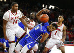 Buffalo guard CJ Massinburg (5) grabs a rebound in between Miami (Ohio) forward Bam Bowman (14) and Nike Sibande (1) during the second half of an NCAA college basketball game, Friday, March 1, 2019, in Oxford, Ohio. Buffalo won 77-69. (AP Photo/Gary Landers)