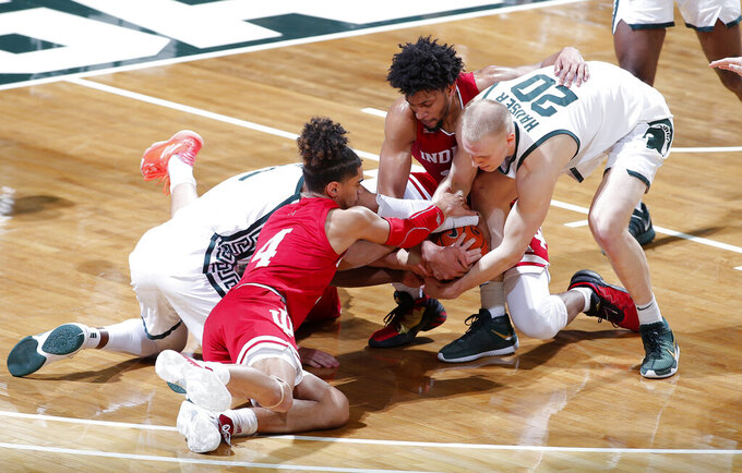 Michigan State's Joshua Langford, left, and Joey Hauser (20) and Indiana's Khristian Lander (4), Jerome Hunter, right rear, and Trey Galloway, center (obscured) vie for the ball during the first half of an NCAA college basketball game, Tuesday, March 2, 2021, in East Lansing, Mich. (AP Photo/Al Goldis)