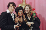 "FILE - In this March 28, 1977, file photo, Sylvester Stallone, left, holds his Oscar for his performance in ""Rocky,"" Eletha Finch, center, holds the Oscar she accepted for her late husband, Peter Finch, who was named best actor for his performance in ""Network,"" and Faye Dunaway  holds the Oscar she won for best actress in ""Network,"" at the Oscars in Los Angeles. ""Hoosiers"" shot all the way to No. 1 in The Associated Press Top 25 of best sports movies, narrowly edging Academy Award Best Picture honoree ""Rocky"" -- released in 1976. (AP Photo/George Brich, File)"