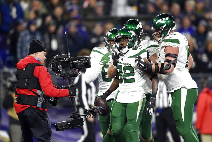 New York Jets wide receiver Jamison Crowder (82) is congratulated by teammates after catching a touchdown pass from quarterback Sam Darnold, not visible, during the first half of an NFL football game against the Baltimore Ravens, Thursday, Dec. 12, 2019, in Baltimore. (AP Photo/Gail Burton)