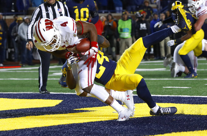 Wisconsin wide receiver A.J. Taylor (4) catches a 3-yard touchdown reception next to Michigan defensive back Lavert Hill (24) during the second half of an NCAA college football game in Ann Arbor, Mich., Saturday, Oct. 13, 2018. (AP Photo/Paul Sancya)