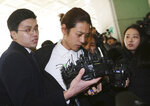 FILE - In this March 14, 2019, file photo, K-pop singer Jung Joon-young, center, arrives at the Seoul Metropolitan Police Agency in Seoul, South Korea. A South Korean court has found two K-pop stars guilty of illicit sexual relations with a woman who was unable to resist and sentenced them to up to six years in prison. The Seoul Central District Court says singer-songwriter Jung received a six-year prison term. (AP Photo/Ahn Young-joon, File)