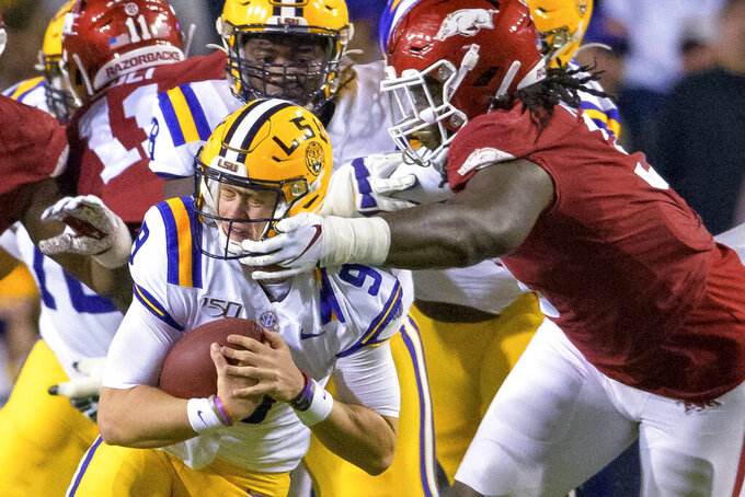 LSU quarterback Joe Burrow (9) tries to get away from Arkansas defensive lineman McTelvin Agim (3) during the first half of an NCAA college football game in Baton Rouge, La., Saturday, Nov. 23, 2019. (AP Photo/Matthew Hinton)
