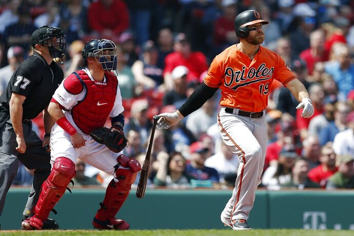 Baltimore Orioles' Chris Davis watches his two-run single in front of Boston Red Sox's Christian Vazquez during the first inning of a baseball game in Boston, Saturday, April 13, 2019. (AP Photo/Michael Dwyer)