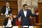 Greek Prime Minister Alexis Tsipras, right, speaks next to Finance Minister Euclid Tsakalotos, during a parliamentary session ,in Athens, on Thursday, June 14, 2018. The head of Greece's main opposition party Kyriakos Mitsotakis submitted a motion for a no-confidence vote in the government, objecting to a deal reached between the prime ministers of Greece and Macedonia to settle a decades-old dispute over Macedonia's name.(AP Photo/Petros Giannakouris)