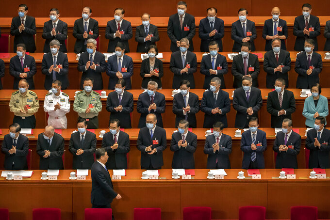 FILE - In this May 28, 2020, file photo, delegates applaud as Chinese President Xi Jinping arrives for the closing session of China's National People's Congress (NPC) in Beijing. The annual gathering of the National People's Congress and its advisory body, the Chinese People's Political Consultative Conference, brings handpicked delegates from across the country to discuss governing priorities and receive instructions from the ruling Communist Party leadership. (AP Photo/Mark Schiefelbein, File)