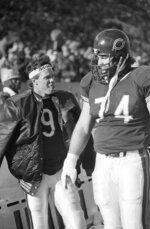 FILE - In this Jan. 5, 1986, file photo, Chicago Bears' quarterback Jim McMahon, left, sticks out his tongue as he and Jim Covert stand on the sidelines during an NFL football game against the New York Giants in Chicago. Covert made the people he played alongside look good, and after a nearly two-decades-long wait, the tough Chicago Bears left tackle will join them in the Pro Football Hall of Fame.  (AP Photo, File)