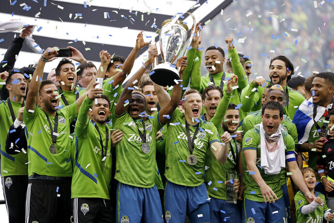 FILE - In this Nov. 10, 2019, file photo, Seattle Sounders players celebrate after beating the Toronto FC in the MLS Cup championship soccer match in Seattle. The Sounders victory was among Washington state's top news stories of 2019. (AP Photo/Elaine Thompson, File)