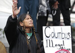 FILE - In this Monday, Oct. 10, 2011 file photo, Ferntree, of Duncan, British Columbia, a member of the Cowichan Tribes, holds her hand up as a prayer is given during a Native American protest against Columbus Day in Seattle. Protest organizers say that Columbus could not have