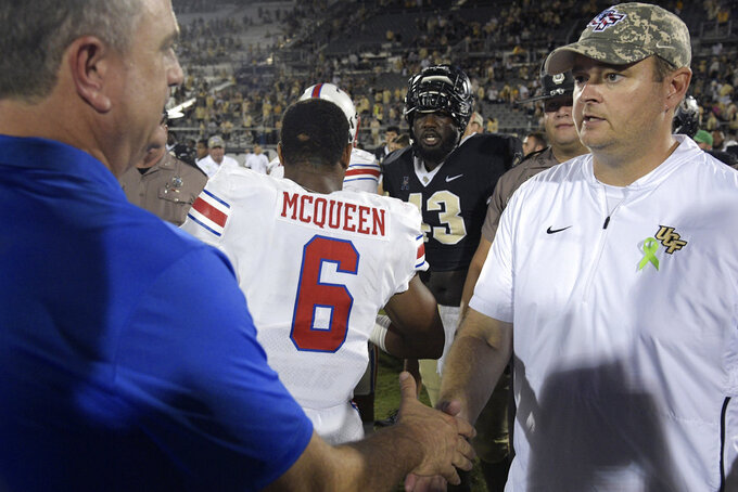 SMU head coach Sonny Dykes, left, shakes hands with Central Florida head coach Josh Heupel on the field after an NCAA college football game Saturday, Oct. 6, 2018, in Orlando, Fla. UCF won 48-20. (AP Photo/Phelan M. Ebenhack)