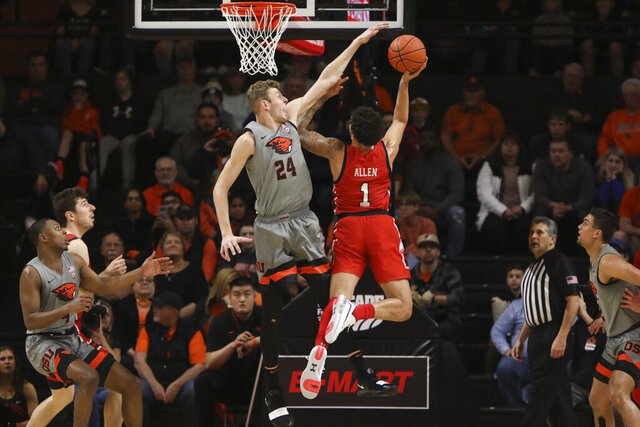 Oregon State's Kylor Kelley (24) blocks a shot by Utah's Timmy Allen (1) during the first half of an NCAA college basketball game in Corvallis, Ore., Thursday, Feb. 13, 2020. (AP Photo/Amanda Loman)