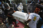 Detained left-wing activist Reina Mae Nasino in handcuffs and wearing a protective suit to prevent the spread of the coronavirus walks beside the coffin of her three-month-old firstborn named River during funeral rites at Manila's North Cemetery, Philippines on Friday Oct. 16, 2020. Left-wing groups on Friday decried the treatment as brutal of Nasino, who was allowed by a Manila court to attend her baby's burial but was restrained with handcuffs, a sweltering protective suit and swarms of armed escorts as she quietly wept. (AP Photo/Aaron Favila)