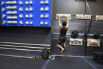 In this June 18, 2019, photo, professional rock climber Alex Honnold works out with weights attached to his harness at the Earth Treks gym in Englewood, Colo. Honnold is trying to get a grip on life in the aftermath of the Academy Award winning documentary