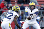 Michigan quarterback Shea Patterson, right, hands off to running back Karan Higdon during the first half of an NCAA college football game against Rutgers, Saturday, Nov. 10, 2018, in Piscataway, N.J. (AP Photo/Julio Cortez)