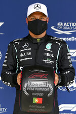 Mercedes driver Valtteri Bottas of Finland poses after he clocked the fastest time during the qualifying session ahead of the Portugal Formula One Grand Prix at the Algarve International Circuit near Portimao, Portugal, Saturday, May 1, 2021. The Portugal Grand Prix will be held on Sunday. (Gabriel Buoys/Pool via AP)