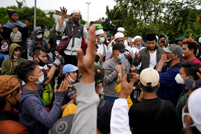 Supporters of firebrand cleric Rizieq Shihab pray near the district court where his sentencing hearing is held in Jakarta, Indonesia, Thursday, June 24, 2021. The influential cleric was sentenced to another four years in prison on Thursday for concealing information about his coronavirus test result. (AP Photo/Dita Alangkara)