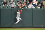 Boston Red Sox left fielder J.D. Martinez (28) and a fan reach for a ball hit by Baltimore Orioles' Jonathan Villar during the first inning of a baseball game, Monday, May 6, 2019, in Baltimore. After review, Villar was called out due to fan interference. (AP Photo/Nick Wass)