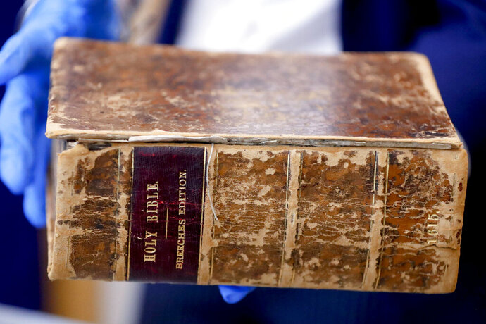 FBI supervisory special agent Shawn Brokos shows the recovered 1615 Breeches Edition Bible during a news conference, Thursday, April 25, 2019, in Pittsburgh. The Bible was stolen from the Carnegie Library in Pittsburgh in the 1990's. It was traced to the American Pilgrim Museum in Leiden, Netherlands. (AP Photo/Keith Srakocic)