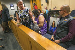 Timothy Hoffman sits next to a picture of his daughter Cynthia Hoffman, during Darin Schilmiller's arraignment for murder charges Friday, Aug. 9, 2019, in Anchorage, Alaska. Schilmiller, a 21-year-old Indiana man charged with masterminding the death of Hoffman, a developmentally disabled Anchorage woman, pleaded not guilty to multiple murder counts. (Loren Holmes/Anchorage Daily News via AP)