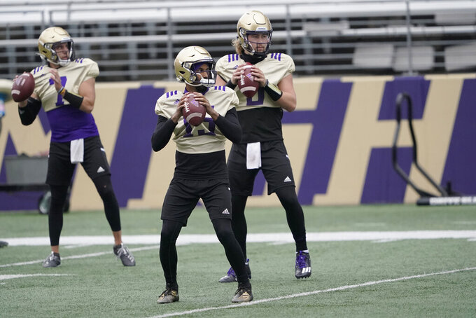 Washington quarterbacks Jaden Sheffey, center, Kevin Thomson, left, and Jacob Sirmon, right, pass in a group during NCAA college football practice, Friday, Oct. 16, 2020, in Seattle. (AP Photo/Ted S. Warren)